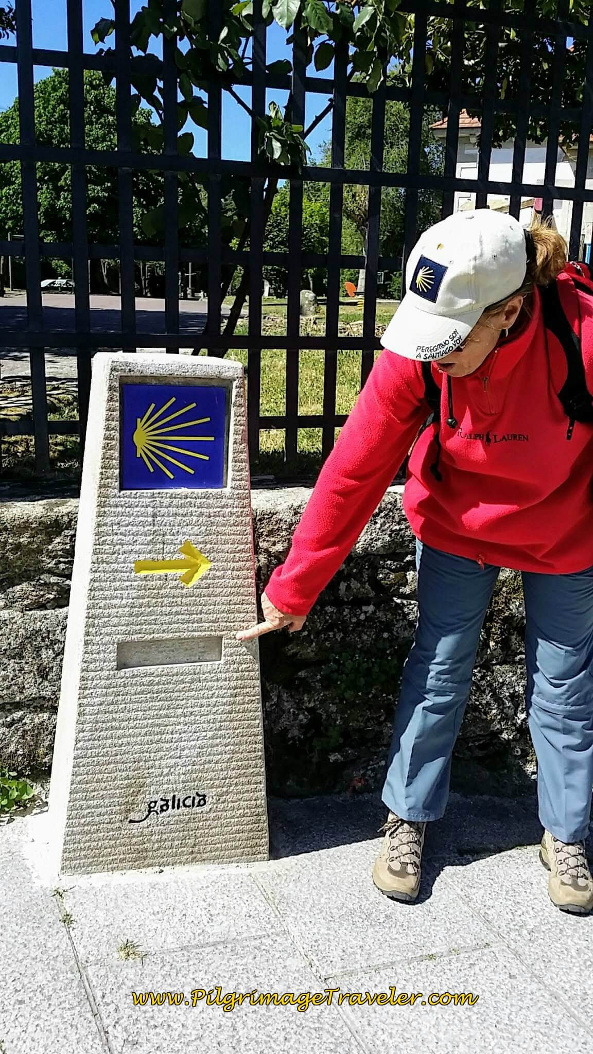 Glyvia pointing to a Camino waymark with kilometer plaque missing on Day Nineteen of the Portuguese Way.