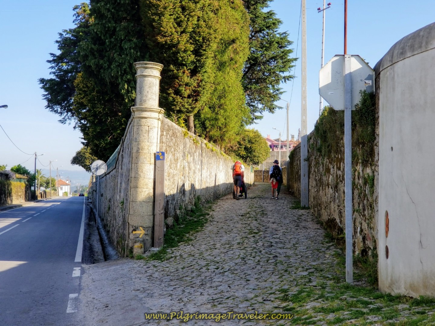 Rich Pushes Magdlena Thru São Mamede on Cobblestone Street on day sixteen on the Central Route of the Camino Portugués