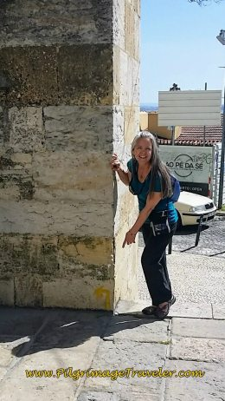 Elle Pointing to Yellow Arrow on the Corner of the Sé de Lisboa