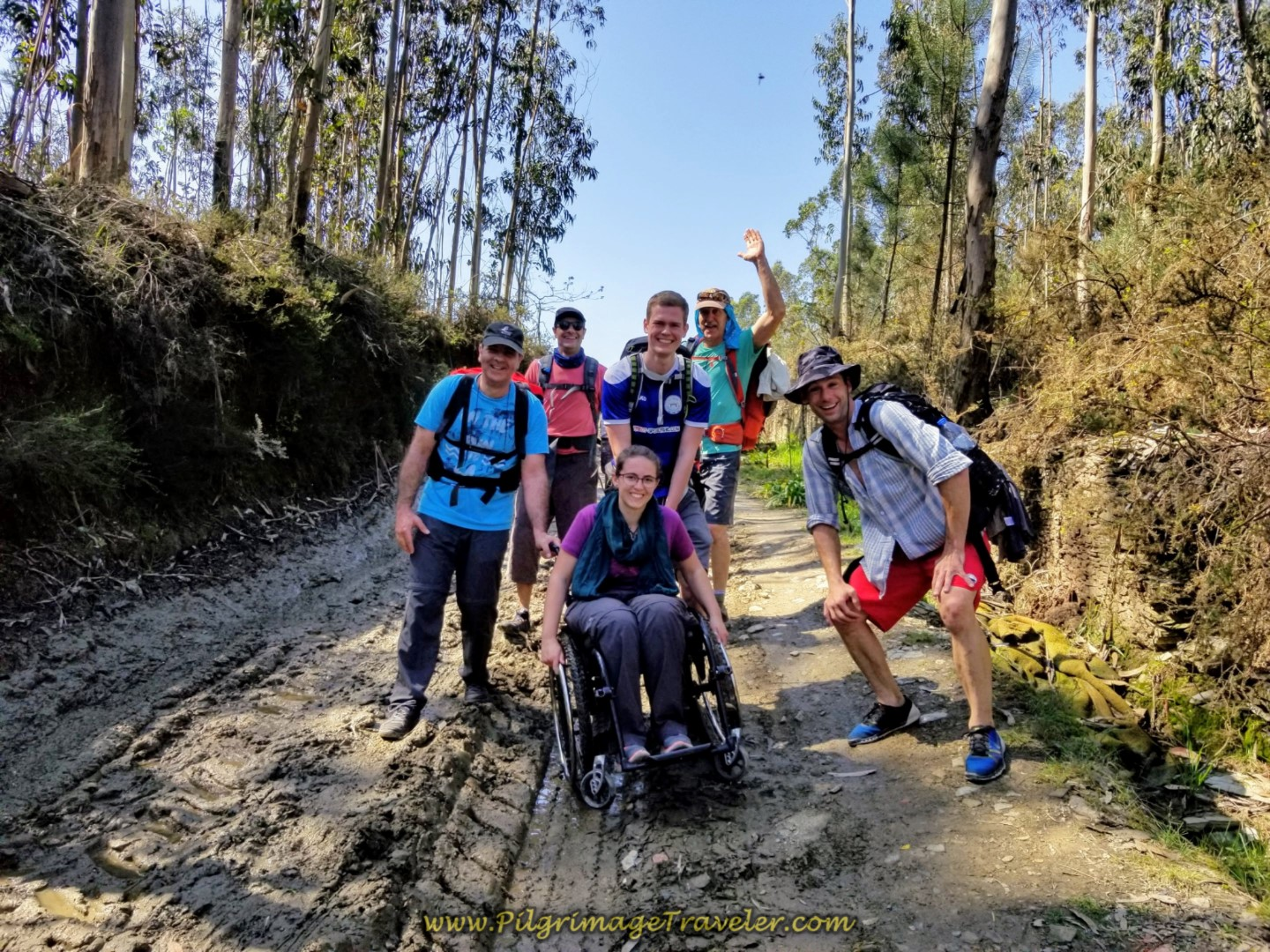 The Magdalena Mud Team guides the wheelchair through the mud and ruts on the Rua Caminho de Santiago on day sixteen of the Central Route of the Portuguese Way
