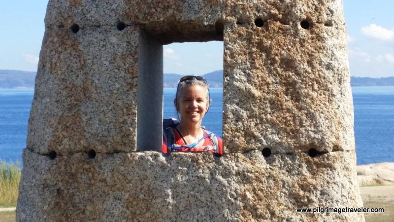 Elle Bieling looking through a Standing Stone, in the Parque de los Menhires, La Coruña, Galicia, Spain
