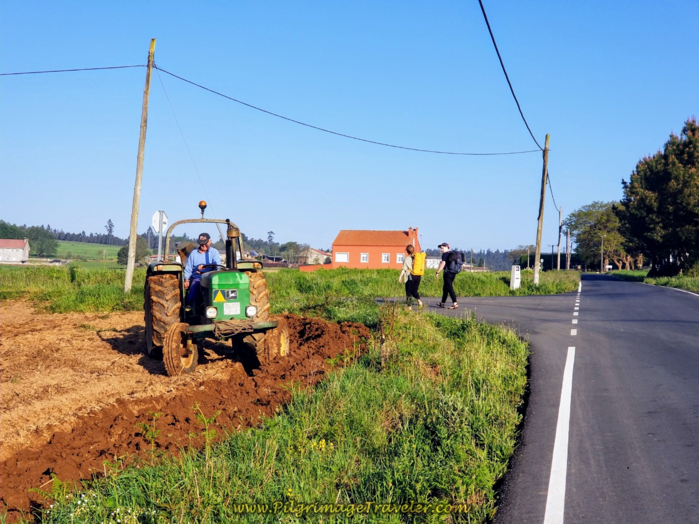 Farmer Plowing as Two Peregrinos Walk By on day eight of the Camino Inglés